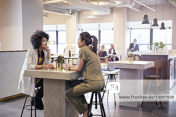 Businesswomen talking while sitting in cafeteria at creative office with colleagues in background