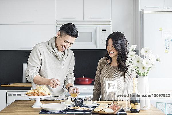 Frau sieht Freund an  der das Frühstück in der Küche vorbereitet