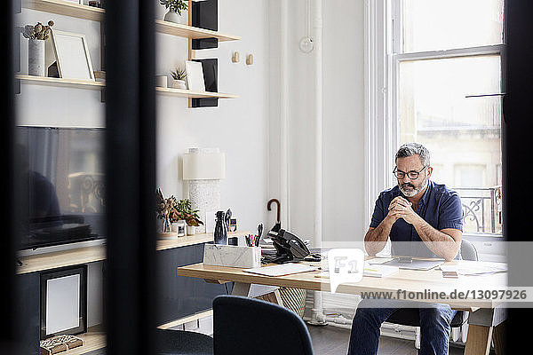 Nachdenklicher Geschäftsmann sitzt am Schreibtisch im kreativen Büro und sieht durch ein Fenster