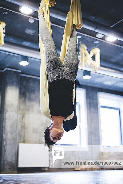 Junge Frau praktiziert Yoga in der Luft  während sie im Fitnessstudio an der Hängematte hängt