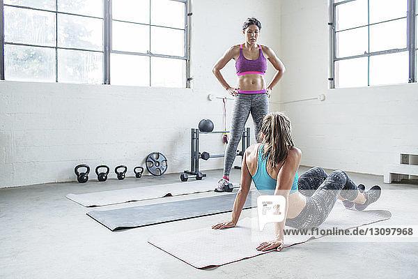 Sportler schaut Freund an  der im Fitnessstudio auf der Trainingsmatte sitzt