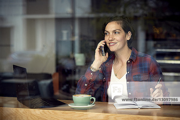 Woman talking on mobile phone while sitting in cafe seen through window