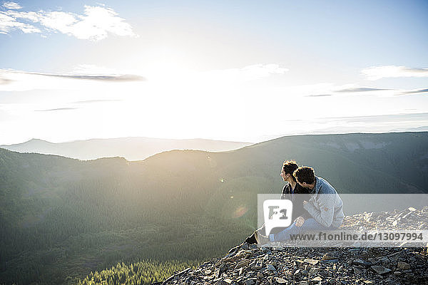 Couple sitting on mountain cliff and looking at view