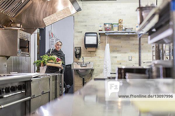 Arbeiter trägt Gemüse in einer Kiste in der Restaurantküche