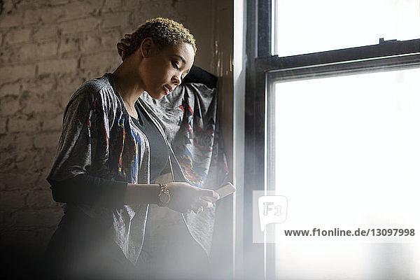 Junge Frau benutzt zu Hause ein Smartphone am Fenster