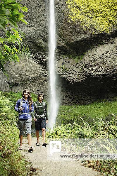 Paar auf Wanderweg am Wasserfall im Wald