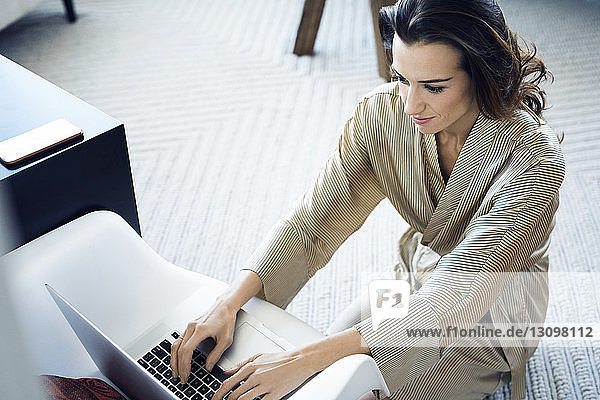 High angle view of woman in bathrobe using laptop computer at home