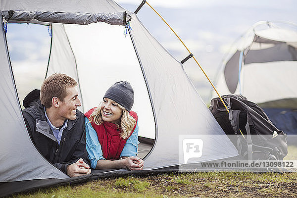 Happy couple relaxing in tent at campsite