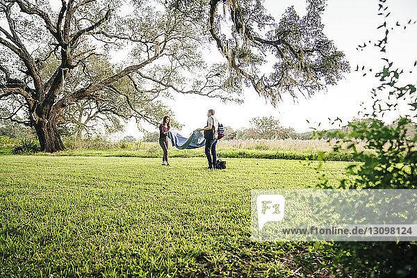 Ehepaar legt Decke auf Grasfeld gegen den Himmel im Park