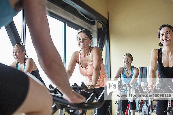 Ein männlicher Ausbilder führt lächelnde Frauen auf Heimtrainern im Fitnessstudio