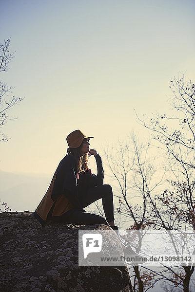 Seitenansicht einer nachdenklichen Frau  die auf einer Klippe gegen den Himmel sitzt