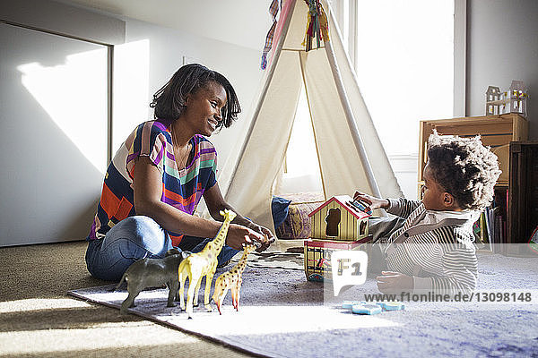 Smiling woman looking at son while playing with toys in bedroom