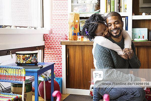 Glückliches Mädchen umarmt Vater zu Hause