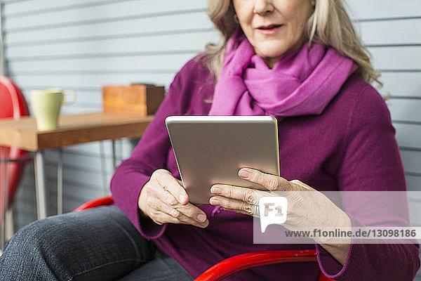 Mittelsektion einer älteren Frau  die einen Tablet-Computer benutzt  während sie auf einem Stuhl auf der Veranda sitzt
