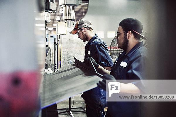 Seitenansicht von Arbeitern  die mit Stahlblech an Maschinen in der Industrie arbeiten