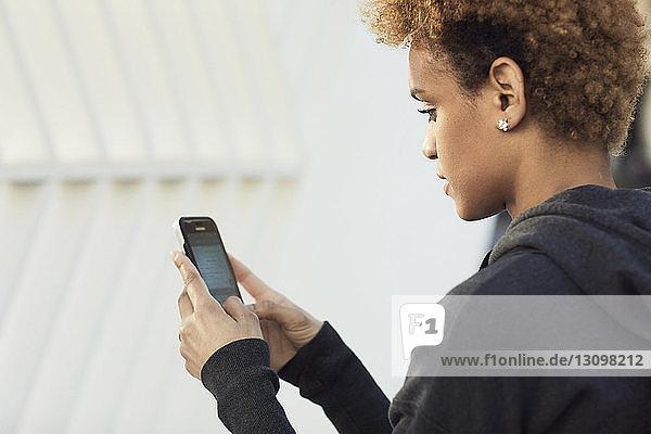 Seitenansicht einer jungen Frau  die an einem sonnigen Tag ein Smartphone in der Stadt benutzt