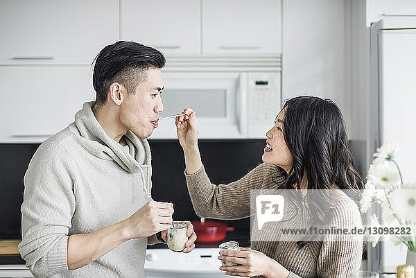 Happy woman feeding breakfast to boyfriend in kitchen