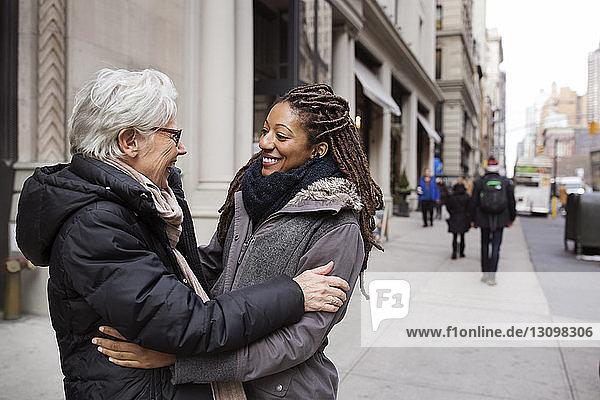 Glückliche Frauen umarmen sich  während sie auf der Straße stehen