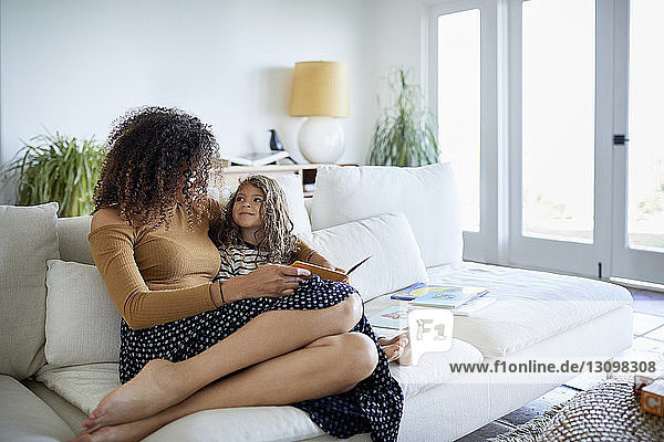 Mother with daughter reading picture book while sitting on sofa at home