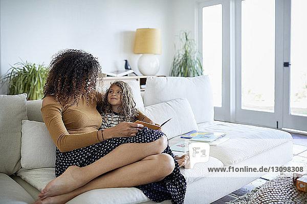 Mutter mit Tochter liest Bilderbuch  während sie zu Hause auf dem Sofa sitzt