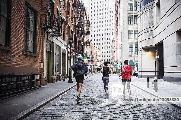 Rückansicht von multi-ethnischen Athleten  die auf der Straße in der Stadt laufen
