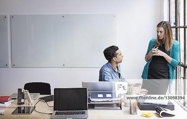 Geschäftsleute diskutieren am Schreibtisch im Büro