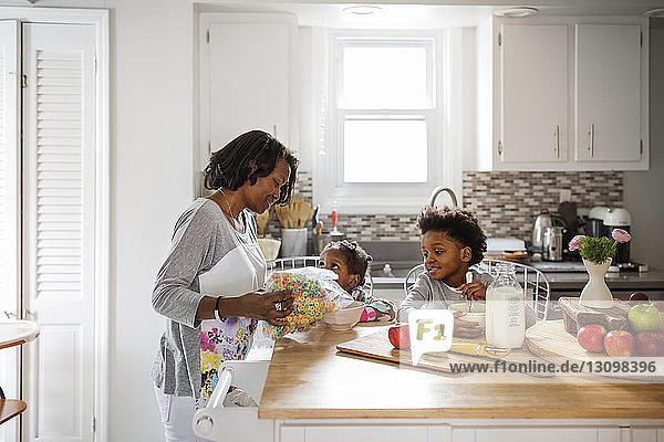 Mother serving breakfast cereals to children at kitchen island