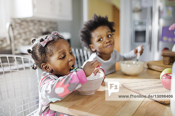 Girl eating breakfast cereals while brother looking at her in kitchen
