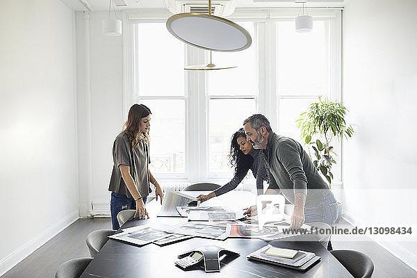 Geschäftsleute prüfen Fotoausdrucke im Konferenzraum