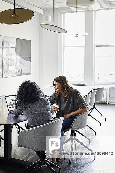 Weibliche Kollegen diskutieren über Laptop-Computer im Konferenzraum des Kreativbüros
