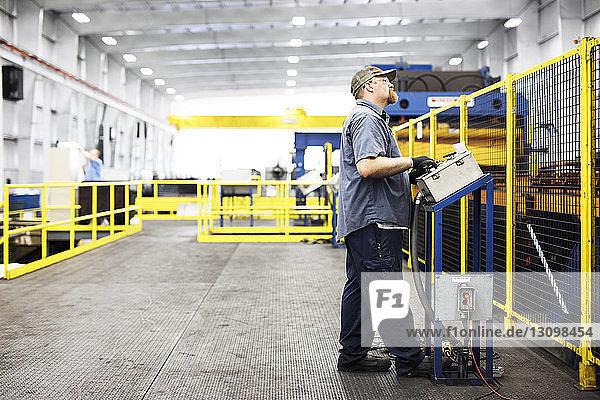 Arbeiter in voller Länge bei der Arbeit in einer Fabrik der Stahlindustrie an einer Kontrollmaschine