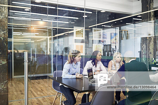 Business people at conference table during meeting seen through glass doors in office