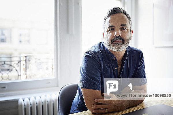 Porträt eines selbstbewussten Geschäftsmannes  der am Schreibtisch im Kreativbüro sitzt