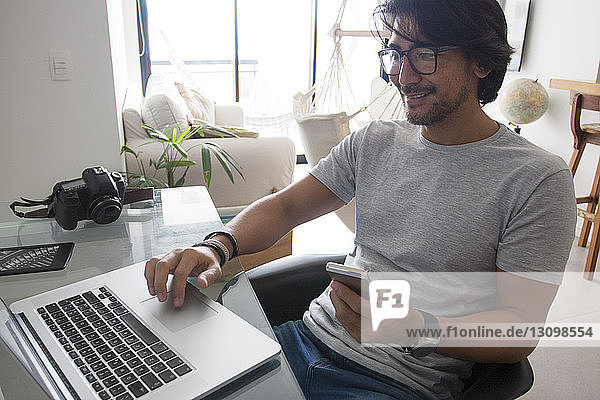 High angle view of smiling man using laptop while working at home