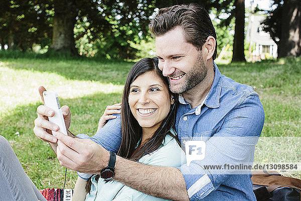 Glückliches Paar  das im Park sitzend Selbsthilfe per Handy nimmt