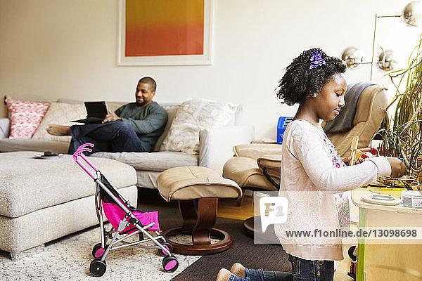 Mädchen spielt mit Spielzeugutensilien  während der Vater einen Tablet-Computer auf dem Sofa benutzt