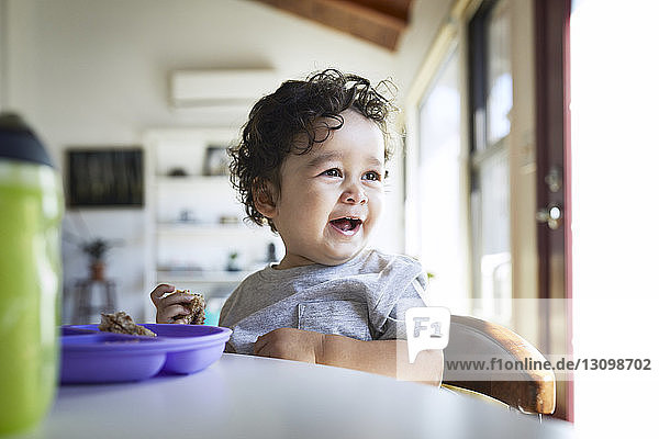 Close-up of cute cheerful baby boy holding breads while looking away at home