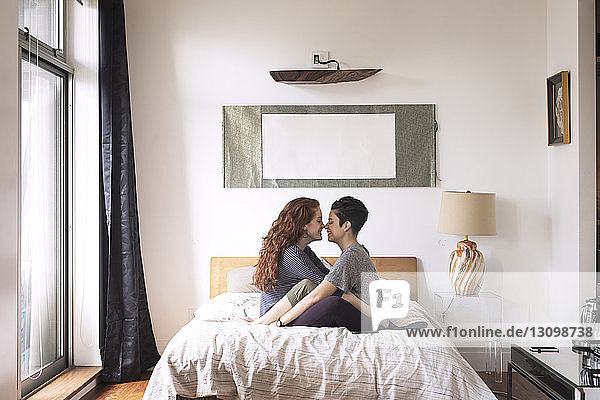 Side view of romantic lesbians rubbing noses while sitting on bed