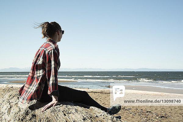 Seitenansicht einer jungen Frau  die aufs Meer schaut  während sie auf einem Felsen vor klarem Himmel sitzt