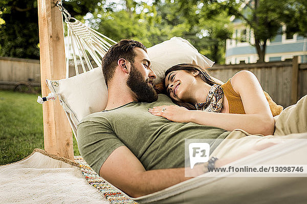 Smiling couple relaxing on hammock at yard
