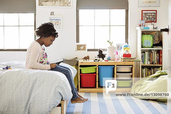 Mädchen benutzt Tablet-Computer  während sie zu Hause am Bett sitzt