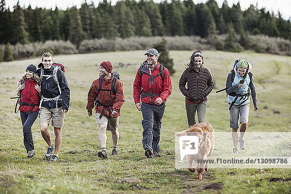Happy friends and dog hiking on field