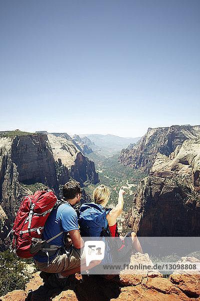 Rückansicht eines Paares  das auf einem Bergfelsen vor klarem Himmel sitzt