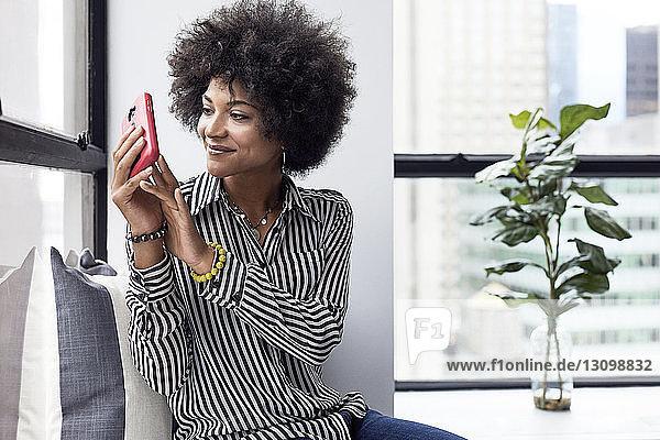 Geschäftsfrau fotografiert mit einem Smartphone  während sie im Büro sitzt