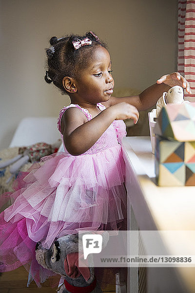 Cute girl in pink dress removing toy from box at home