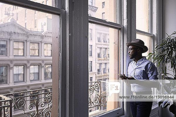 Geschäftsmann benutzt Mobiltelefon  während er im Kreativbüro am Fenster steht