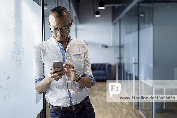 Businessman using smart phone while standing at office corridor