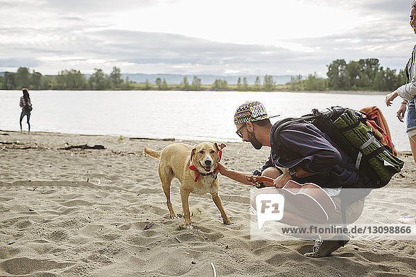 Side view of man stroking dog while crouching on sand at riverbank