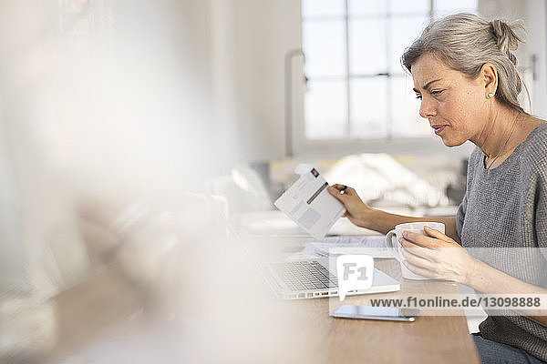 Concentrated woman working in at table in home office