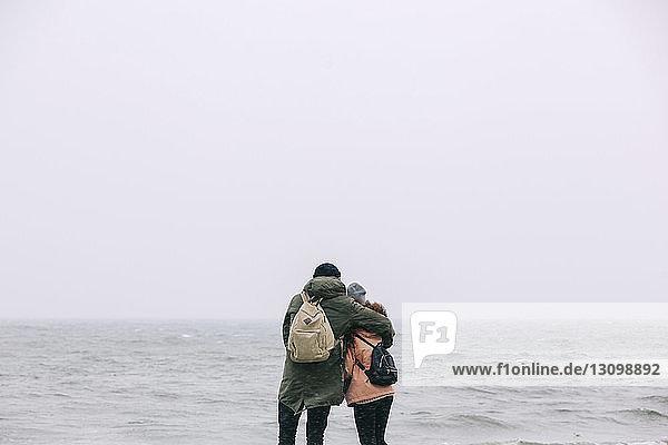 Rückansicht eines Paares  das gegen das Meer und den klaren Himmel steht